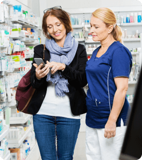 smiling female customer showing smart phone to the pharmacist